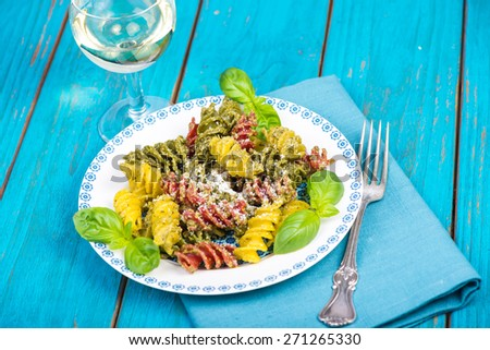 Italian pasta with pesto and parmesan cheese served on plate - stock photo