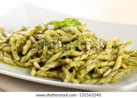 italian pasta with pesto sauce on white dish - stock photo