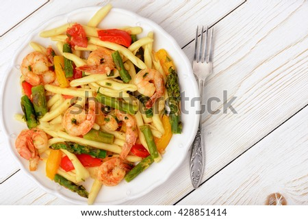 Italian pasta with shrimps, asparagus, paprika and tomatoes.