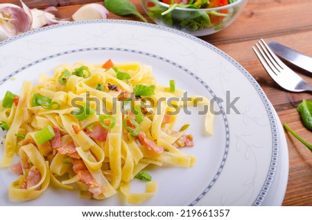 Italian pasta with spring onion, garlic and bacon with salad