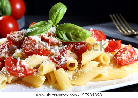 italian  pasta with tomato and cheese dark background - stock photo
