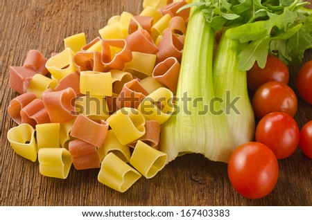 Italian pasta with vegetables on a wooden background