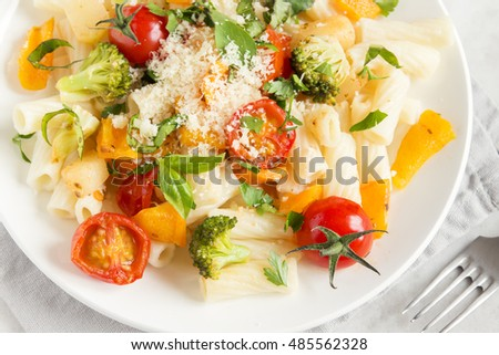 Italian pasta with vegetables (tomatoes, broccoli, pepper and greens) and parmesan cheese on white background - healthy vegetarian food