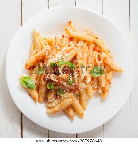Italian penne pasta or noodles with a savory tomato sauce, fresh basil and grated parmesan cheese viewed close up from above on a white plate in square format - stock photo