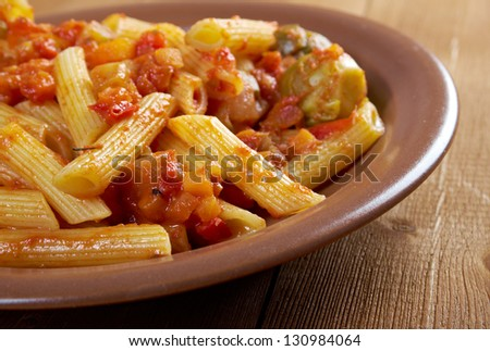 Italian Penne rigate pasta  with  vegetable  tomato sauce  on wooden table