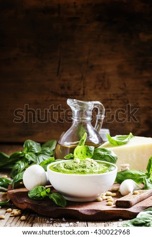 Italian pesto sauce in a white porcelain bowl, ingredients for cooking, vintage wooden background, selective focus - stock photo