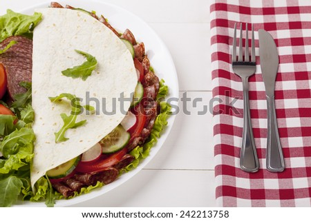Italian Piadina Romagnola with salami and vegetables on white woodboard - stock photo
