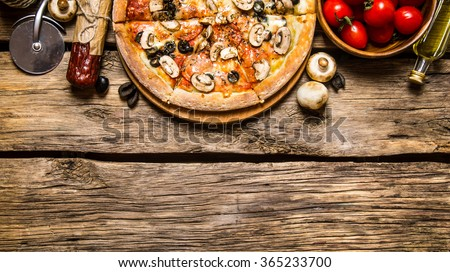 Italian pizza and different ingredients - meat, mushrooms, tomatoes and olive oil. On wooden background. Free space for text . Top view - stock photo