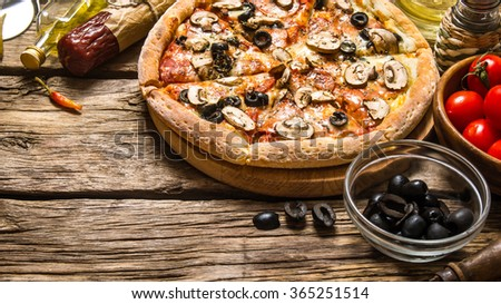 Italian pizza and different ingredients - meat, mushrooms, tomatoes and olive oil. On wooden background. - stock photo