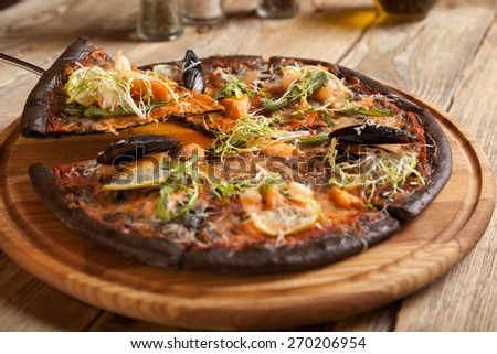 "Italian pizza ""Di Mare"" with black dough on wooden table.  - stock photo"