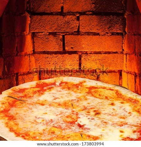 italian pizza margherita and hot brick wall of wood burning oven - stock photo