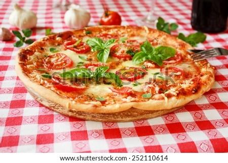 Italian Pizza Margherita with basil and fresh tomatoes - stock photo