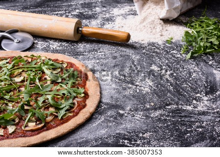 Italian pizza with arugula (rucola) and mushrooms on wooden table. Copy space.