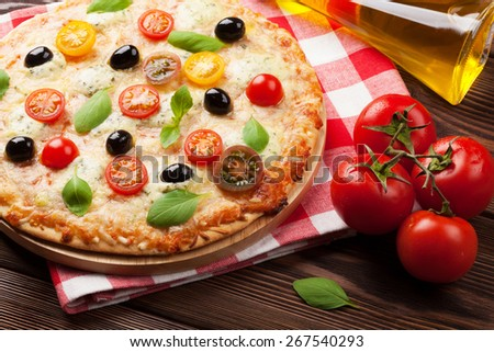 Italian pizza with cheese, tomatoes and basil on wooden table