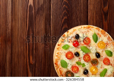 Italian pizza with cheese, tomatoes, olives and basil on wooden table. Top view with copy space