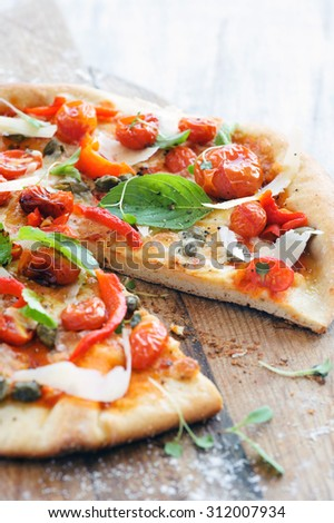 Italian pizza with fresh herbs, roasted tomatoes, peppers, capers and shaved cheese - stock photo