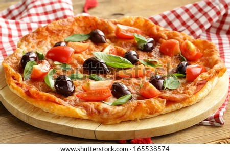 Italian pizza with olives and tomatoes on wooden board