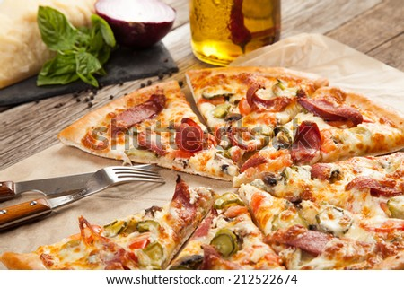 Italian pizza with pepperoni meat and vegetables on an old vintage wooden table with ingredients - stock photo
