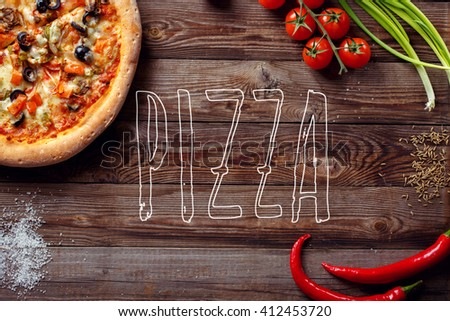 Italian pizza with tomatoes on a wooden table, top view, close-up - stock photo