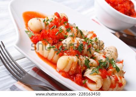 Italian potato gnocchi in tomato sauce on a white plate. closeup. horizontal  - stock photo