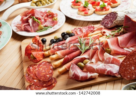 Italian prosciutto, cured pork meat on cutting board - stock photo