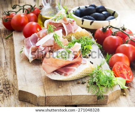 Italian Prosciutto Ham Appetizer with Spices on a Wooden Cutting Board Ready to be Served - stock photo