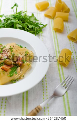 Italian rigatoni with parmesan cheese, parma ham and mushrooms, arugula and microgreens sprinkled