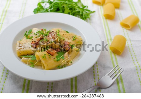 Italian rigatoni with parmesan cheese, parma ham and mushrooms, arugula and microgreens sprinkled - stock photo