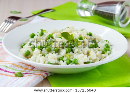 Italian risotto with rice, green peas, mint and cheese, homemade dinner - stock photo