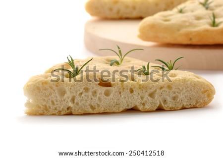 Italian rosemary Focaccia bread on a wooden board. - stock photo