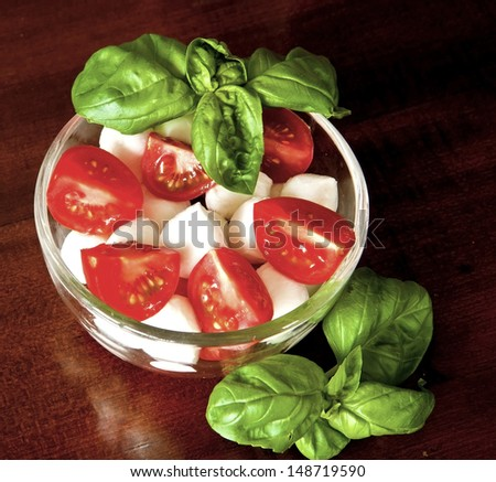 Italian salad with absolute fresh summer ingredients: mozzarella, ripe red tomatoes and basil - stock photo
