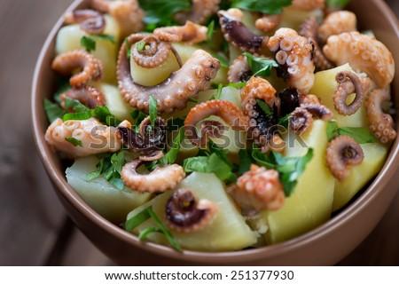 Italian salad with sliced octopus, potato and parsley, close-up - stock photo