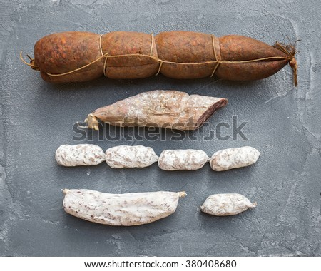 Italian salami sausages of different kinds over a rough grey concrete textured background, top view, horizontal - stock photo