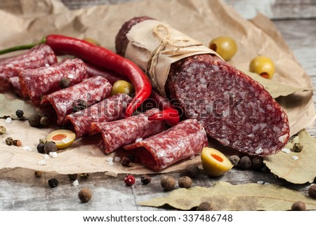Italian salami with olives and spices on wooden background - stock photo