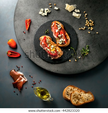 Italian sandwich/bruschetta with smoked meat and ingredients: ciabatta, thyme, paprika, Parmesan and Gorgonzola cheese, olive oil and spices over grey grunge background. Top view. Square composition - stock photo