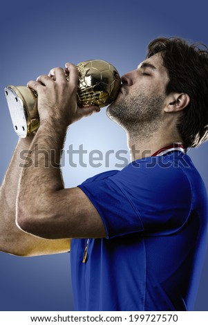 Italian soccer player, celebrating the championship with a trophy in his hand. On a blue background.