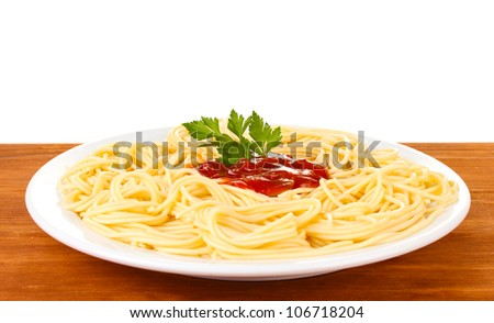 Italian spagetti cooked in a white plate on wooden background