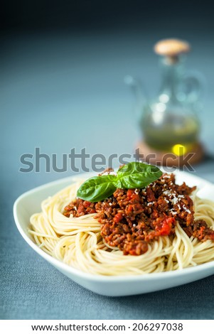 Italian spaghetti Bolognaise with a delcious tomato based meat sauce on spaghetti noodles topped with grated parmesan and fresh basil and served with olive oil - stock photo