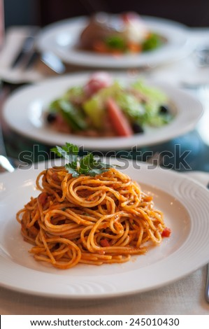 Italian spaghetti in tomato sauce in a plate with many other dishes in the background. - stock photo