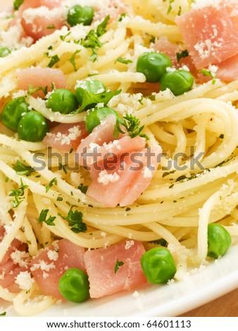 Italian spaghetti with ham and green peas. Shallow dof. - stock photo