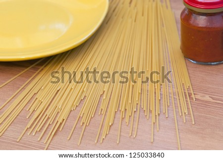 Italian spaghetti with tomato sauce and yellow bowl on the table. - stock photo