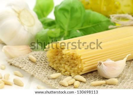 Italian spaghetti with typical pesto sauce ingredients - pine nuts, garlic, fresh basil and olive oil at the background