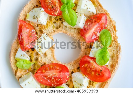 Italian starter friselle. Classical frisella tomato, cheese mozzarella and basil with oregano and olive oil. Dried bread called freselle on white plate. Italian food. Healthy vegetarian food. - stock photo