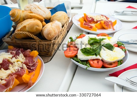 italian starters and bread on a set table - stock photo