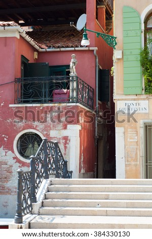 Italian street with bridge and stairs and signpost