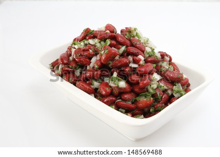 Italian style, cold red beans salad with parsley, onion and olive oil. taken on white background