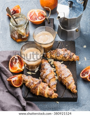 Italian style home breakfast. Latte coffee, almond croissants and red bloody oranges on dark wooden serving  board over concrete textured table, moka pot and honey jar at background, selective focus - stock photo