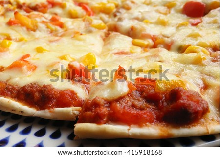 Italian style pizza and corn grain, beef, peppers and tomatoes. Close-up Pizza, blur, selective focus.
