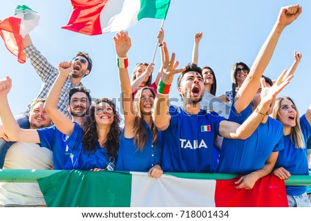 Italian supporters celebrating at stadium with flags. Group of fans watching a match and cheering team Italy. Sport and lifestyle concepts.