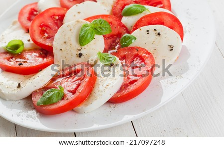 Italian tomato and mozzarella Caprese salad seasoned with pepper and salt and garnished with leaves of fresh basil on a white plate - stock photo
